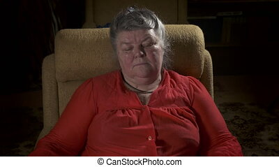 Elderly overweight woman sitting in armchair relaxing in front of TV at home