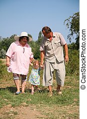 elderly pair goes for a walk with the granddaughter