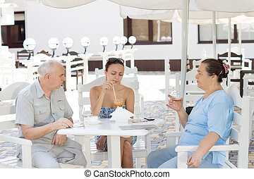 Elderly parents lunching with their daughter