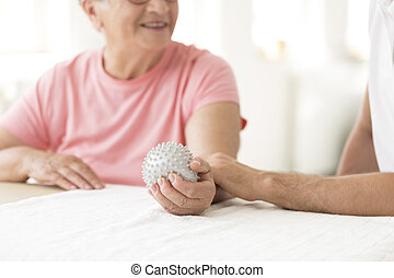 Elderly patient holding grey ball