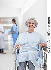 Elderly patient in a wheelchair in a corridor