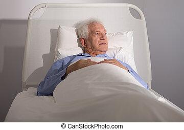 Elderly patient in bed - Elderly sick male patient lying in ...