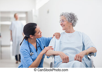 Elderly patient looking at a nurse in hospital ward
