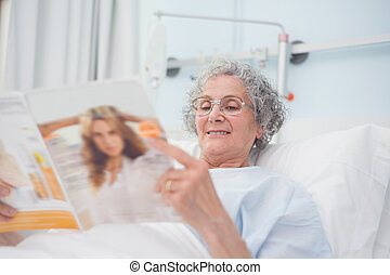 Elderly patient reading a magazine on her bed in hospital...