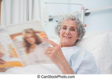 Elderly patient reading a magazine