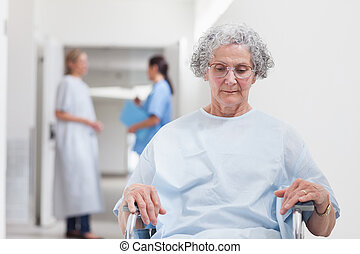 Elderly patient sitting in a wheelchair in hospital ward