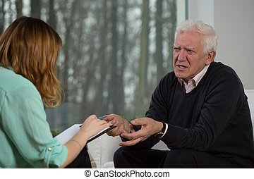 Elderly patient talking with psychotherapist about his troubles