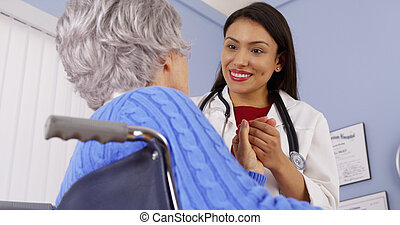Elderly patient thanking Mexican woman doctor