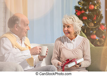 Elderly people giving presents