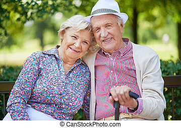 Elderly people - Happy seniors sitting in the park and...