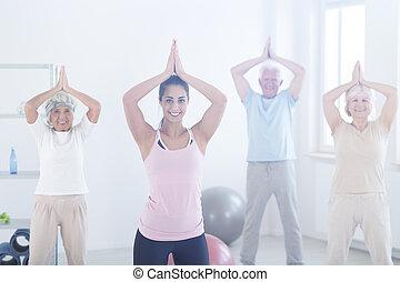 Elderly people in yoga pose