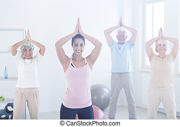 Elderly people in yoga pose - Group of elderly people and...