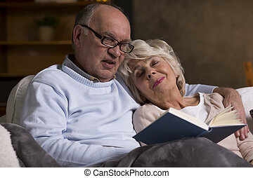 Elderly people reading book