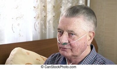 Elderly person puts a nasal catheter with oxygen on his head at home. Theme of a serious and incurable disease of lungs and respiratory system. Grandfather breathes in a special medical mask