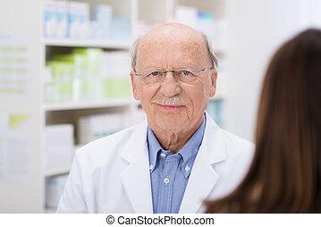 Elderly pharmacist serving a patient