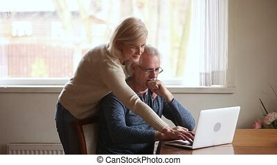 Elderly positive couple using computer new application or...