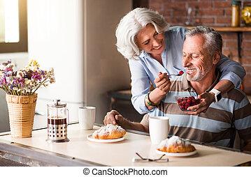 Elderly positive woman feeding her lovely husband.