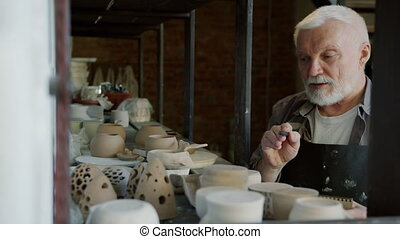 Elderly potter in dirty apron counting pots in workshop ...