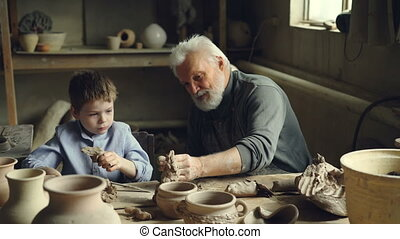 Elderly potter is teaching his grandson how to roll clay...
