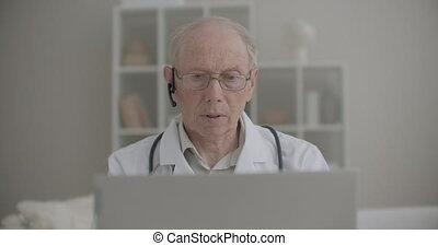 elderly professor of medicine is using laptop for online consulting of patients and intern students from his office