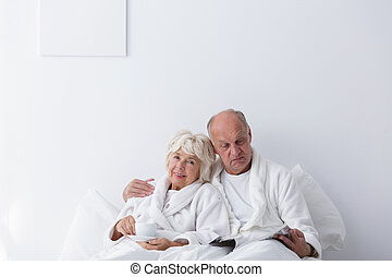 Elderly romantic couple in bedroom