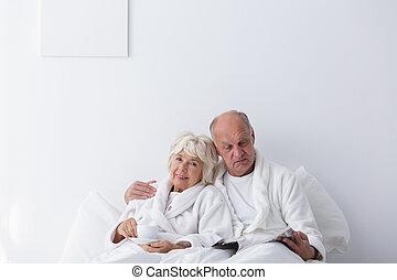 Elderly romantic couple in bedroom