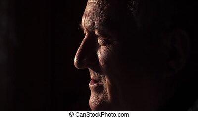 Elderly sad man in the dark