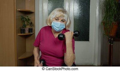 Retired senior woman in medical mask doing workout, training, fitness, sport activity exercises at home. Elderly old grandmother making weight lifting dumbbells exercising during coronavirus lockdown