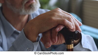 Elderly senior adult man holding walking cane stick in hands concept, sad depressed lonely old retired disabled male grandparent sit alone at home waiting medical care support concept, close up view