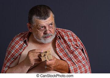 Elderly senior man holding wooden massager