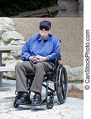 Elderly senior man in wheelchair sitting outside