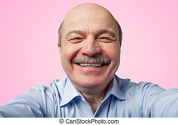 Elderly senior man with a mustache holding a smartphone and makes selfie