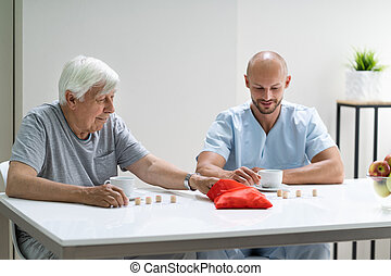 Elderly Senior Playing Lotto With Caregiver