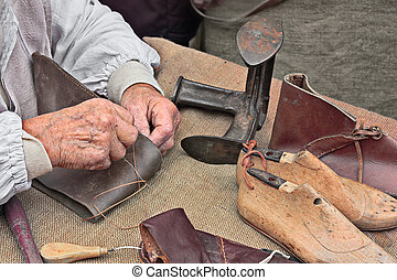 elderly shoemaker makes artisan shoes on an old bench with...