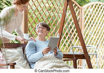 Elderly sitting on hanging bench