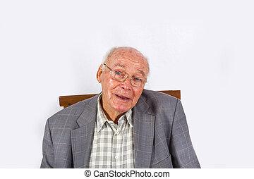 elderly smart confident man sitting in his armchair