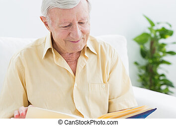 Elderly smiling man watching his album on a sofa