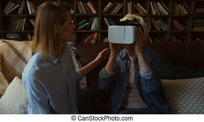 Elderly smiling woman testing VR glasses with her daughter