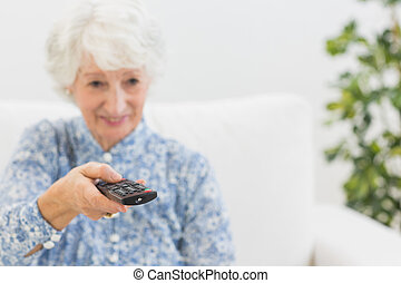 Elderly smiling woman using the remote