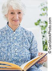 Elderly smiling woman with photo album