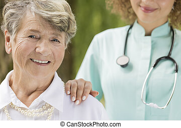Elderly smiling woman with the doctor - Close shot of...