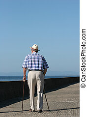 Elderly Struggle - Rear view of an elderly disabled man ...