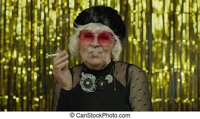 Elderly style mature businesswoman in fashion black clothes in sunglasses posing, smoke cigarette