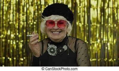 Elderly style mature grandmother in fashion black clothes in sunglasses posing, smoke cigarette