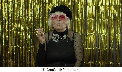 Elderly style mature granny in fashion black clothes in sunglasses posing, smoke cigarette