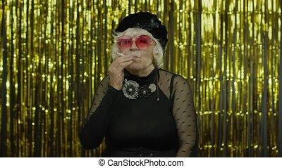 Elderly style mature woman in fashion black clothes in sunglasses posing, smoke cigarette
