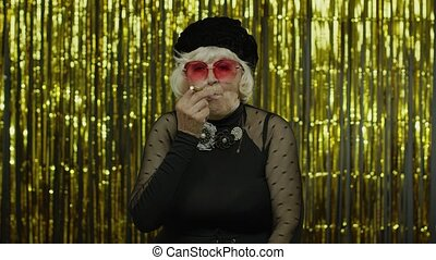 Elderly style mature woman in fashion clothes in sunglasses posing, smoke electronic cigarette