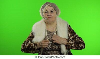 Elderly stylish grandmother. Caucasian woman smoke cigarette, dance. Chroma key