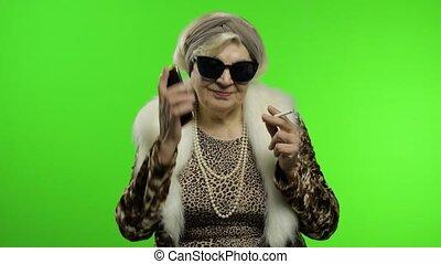 Elderly stylish trendy caucasian grandmother woman using smartphone. Chroma key