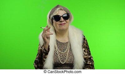 Elderly stylish trendy grandmother. Caucasian woman smoke cigarette. Chroma key